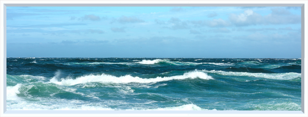 Turquoise waves under a pale blue sky with faint, grey clouds