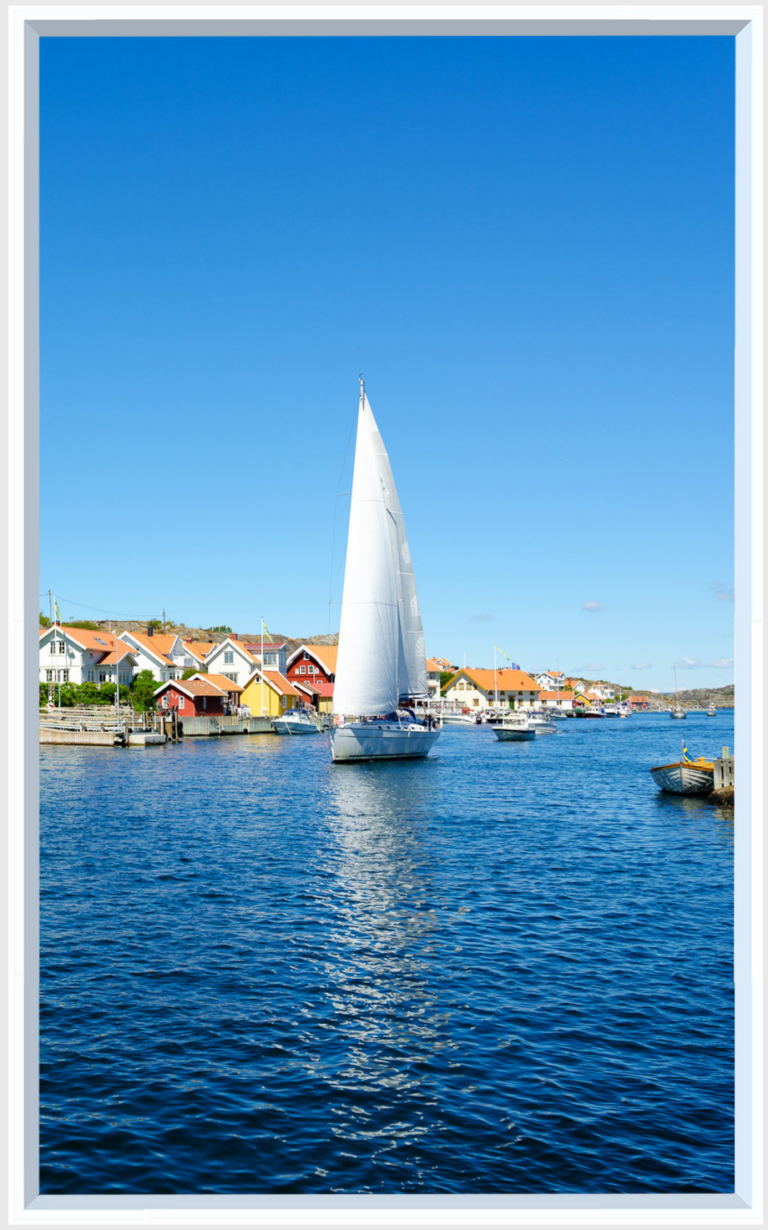 Window imagery of a tall sailing boat on bright blue water under a cloudless sky