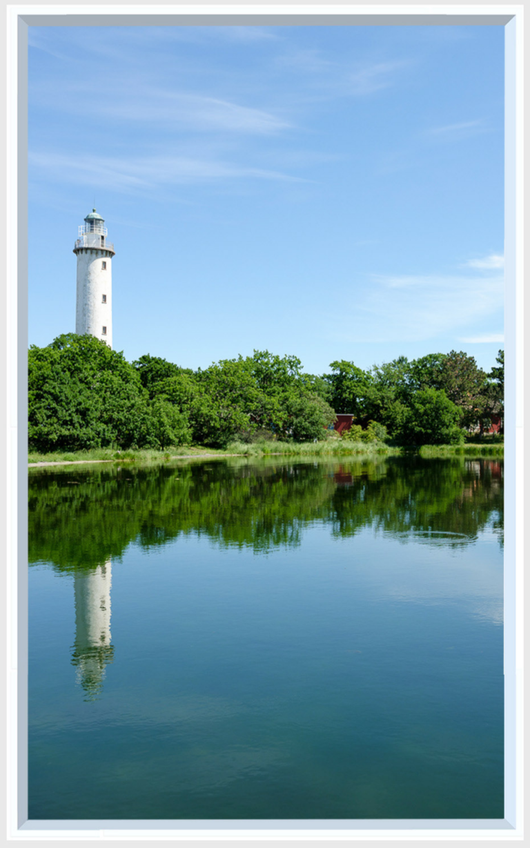 Lighthouse view reflecting in the water with trees for a luminous virtual window